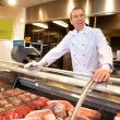 View of frozen meat with cheerful chef - Stock Photo