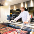 Cheerful chef on the counter of frozen meat — Stock Photo