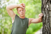 Tired man leaning on tree — Stock Photo