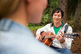 Man Playing Guitar for Woman — Stock Photo