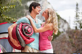 Romantic couple with sleeping bag while camping — Stock Photo