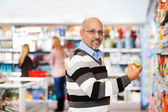 Smiling mature man shopping in the supermarket — Stockfoto