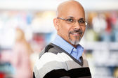 Mature man smiling while shopping — Stock Photo