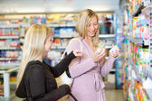 Young women smiling while shopping together — Stock Photo