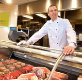 View of frozen meat with cheerful chef — Stock Photo