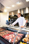 Cheerful chef on the counter of frozen meat — Stockfoto