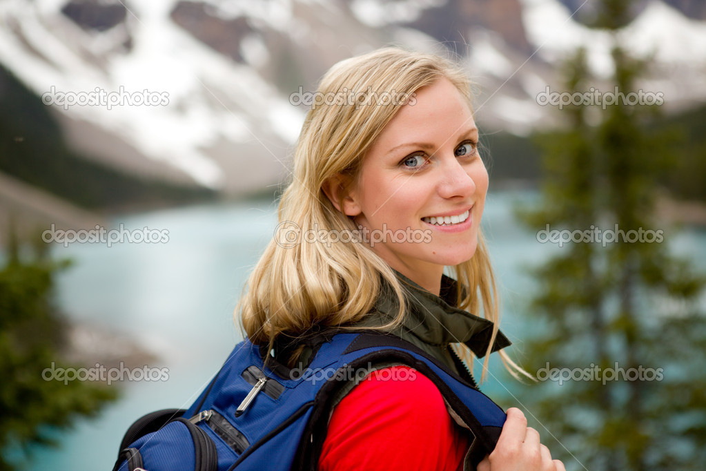 A portrait of a pretty woman in front of a mountain landscape, Lake Moraine, Alberta, Canada  Stock Photo #5710926
