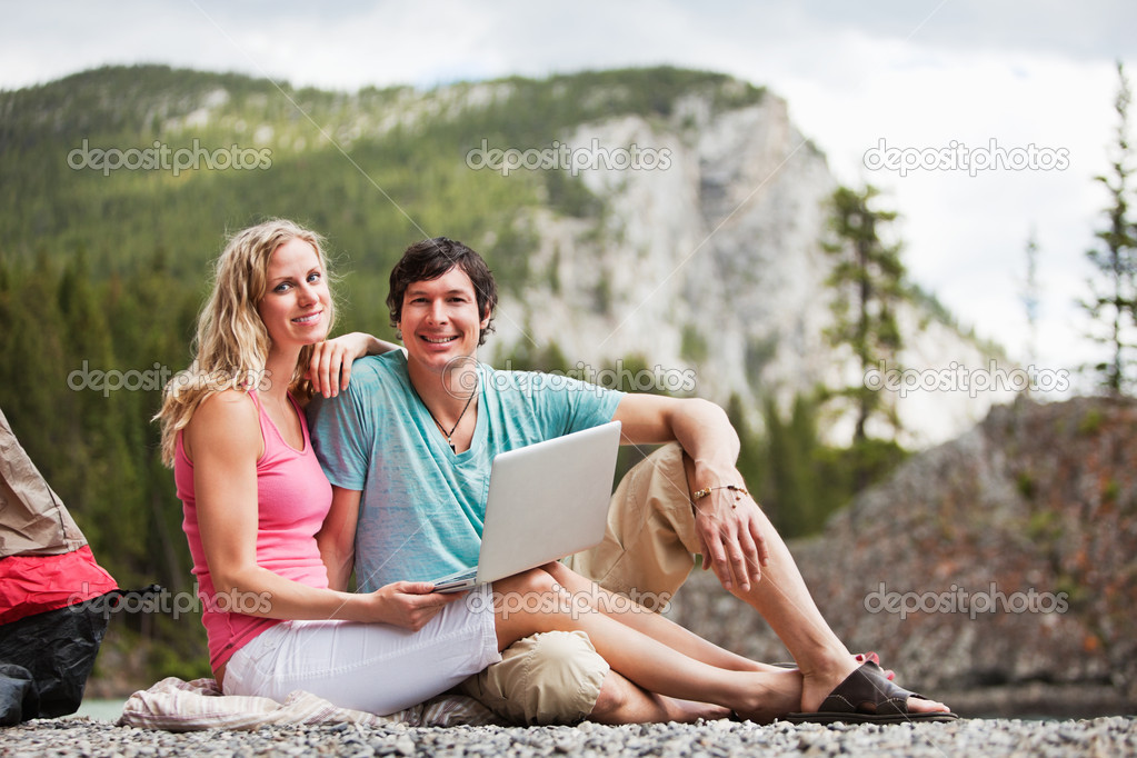 Portrait of happy relaxed young couple with laptop while camping — Stock Photo #5711398