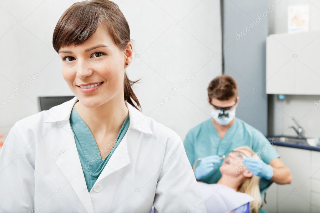 Portrait of a dental assistant smiling with dentistry work in the background — Stock Photo #5712043