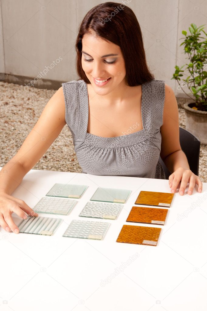 A female architect designer choosing a glass tile from a group of samples — Stock Photo #5712702