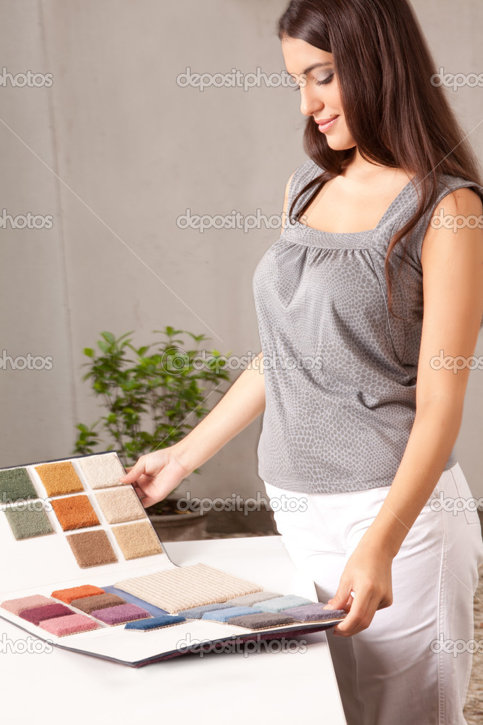 A female interior designer looking at carpet swatches in a catalogue — Stock Photo #5712806