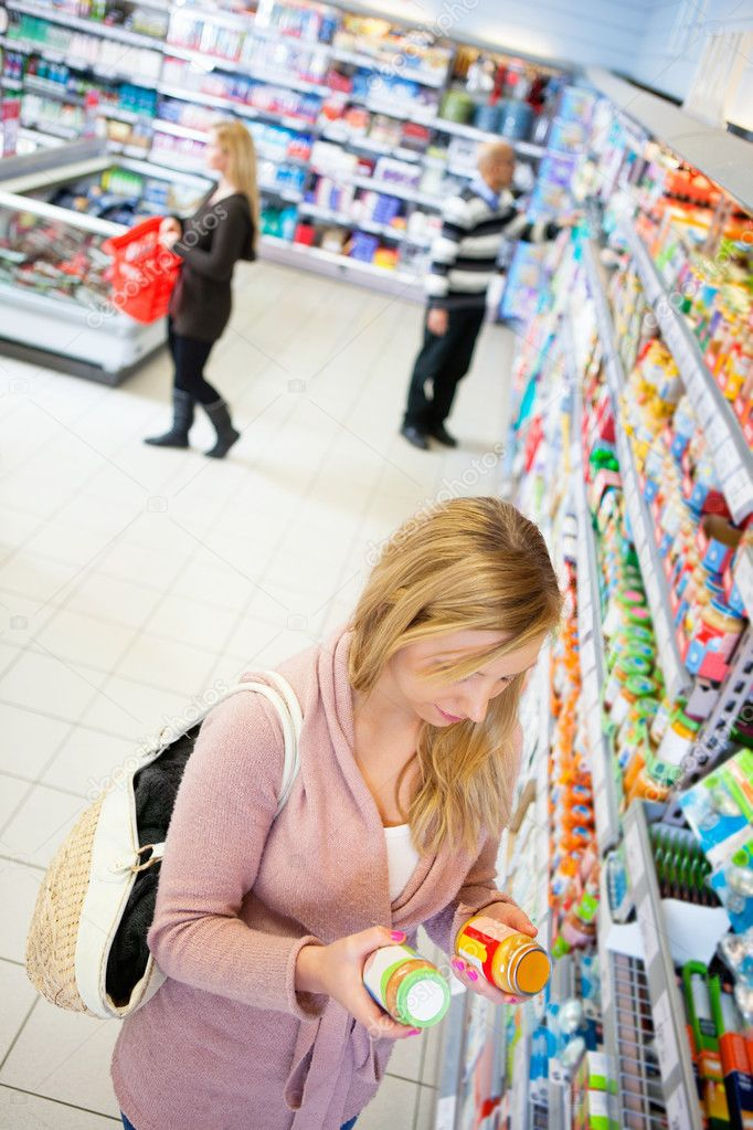 High angle view of a woman comparing products in a grocery store — Stock Photo #5713863