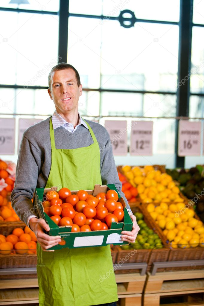 A friendly grocery store owner with a box of ripe tomatoes  Stock Photo #5714425