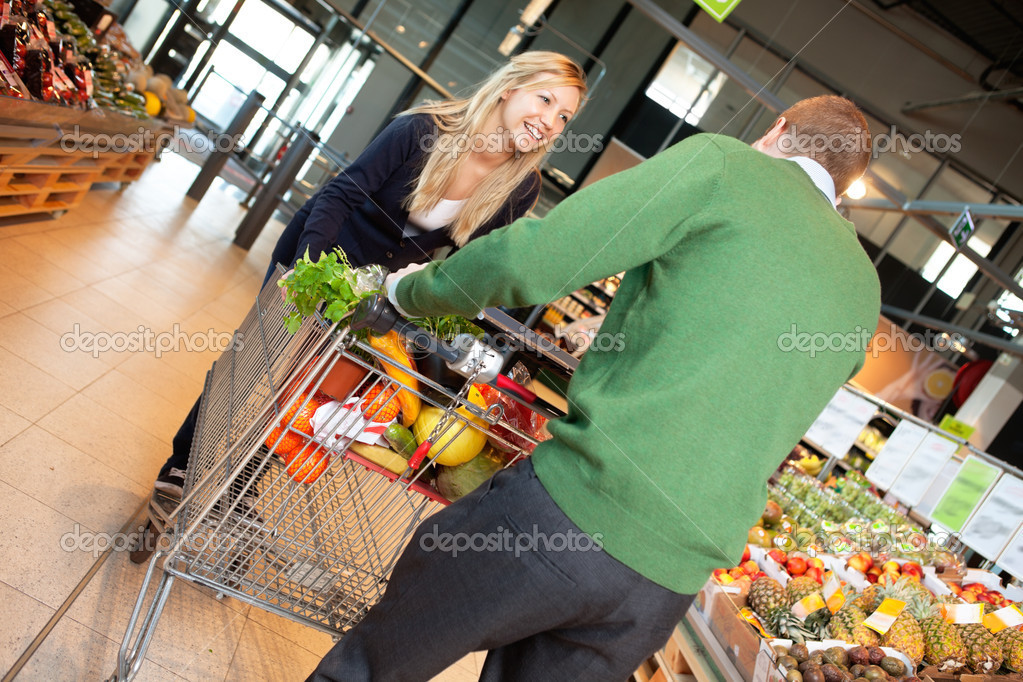 Man and woman in playful mood pushing shopping cart in shopping store — Stock Photo #5716697
