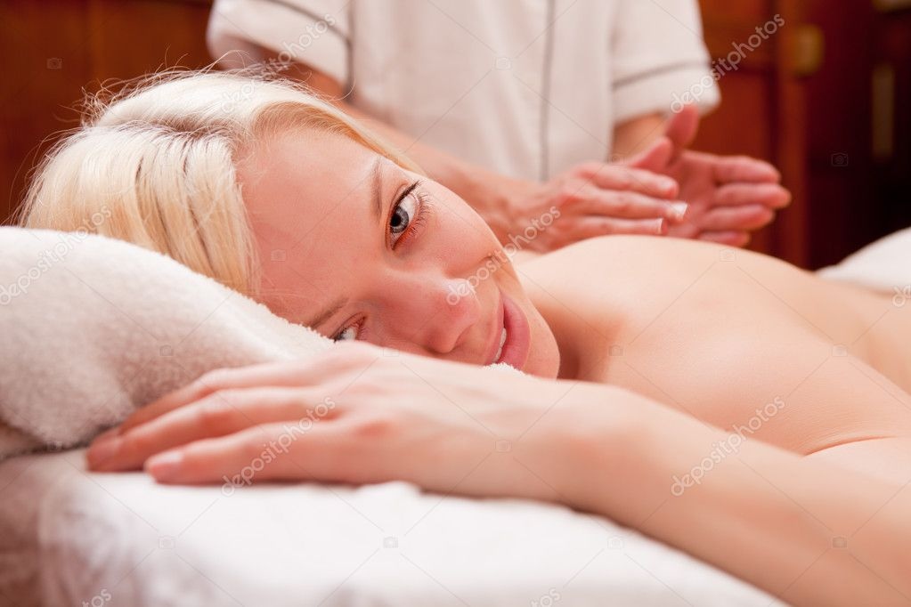 A blond female looking at the camera, receiving a percussive back massage in a spa — Stock Photo #5718866
