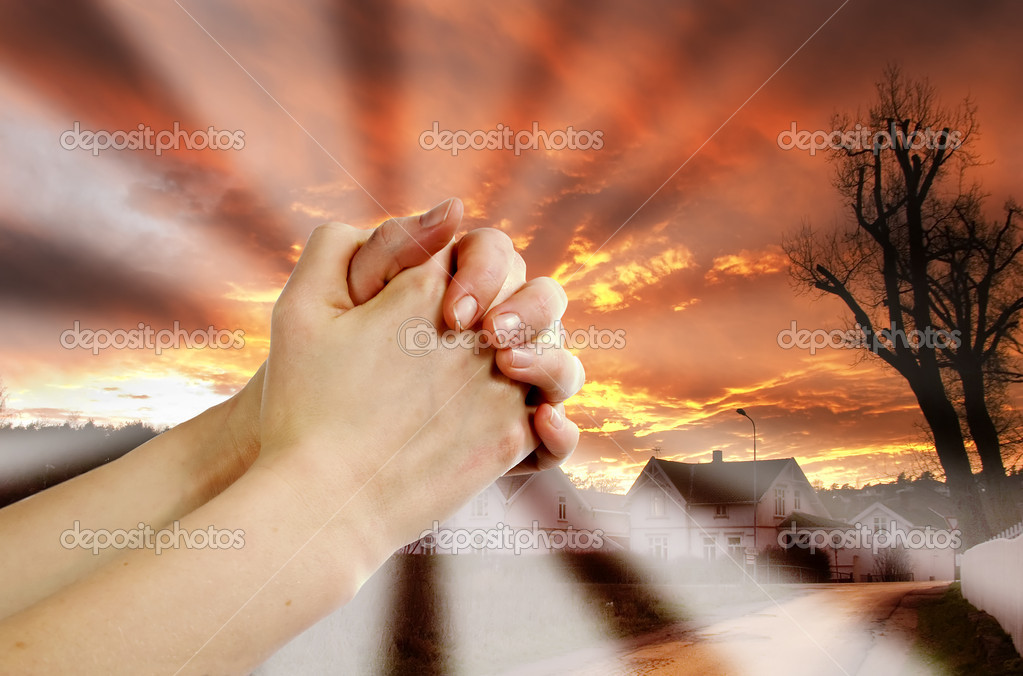 Hands praying with a dramatic red sky overa small town — Stock Photo #5724132
