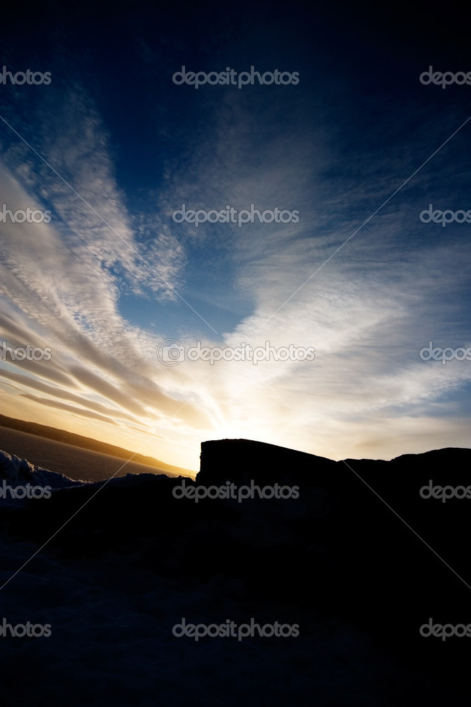 A rock landscape near the ocean during a sunset and a dramatic sky.  Stock Photo #5724195