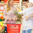 Two Friends Buying Groceries with Baby — Stock Photo