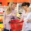 Mother carrying child with friend while shopping — Stockfoto