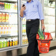 Man with Grocery Basket and Mobile Phone — Stock Photo