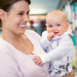 Cheerful mother and baby in shopping centre — Stock Photo