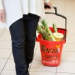 Woman in Supermarket pulling Basket — Stock Photo