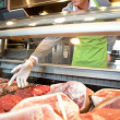 Market assistant picking meat — Stock Photo