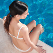 Young woman sitting at the edge of poolside - Stock Photo