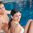 Beautiful young couple relaxing by the poolside - Stock Photo