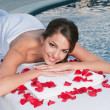 Smiling young woman at spa with rose petals around — Stock Photo