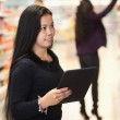 Woman using digital tablet in shopping centre — Stock Photo