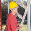 Male construction worker with a ladder - Stock Photo