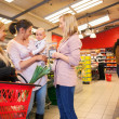Mother carrying child with friends shopping — Stockfoto