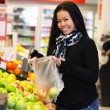 Asian Woman in Supermarket - Stock Photo