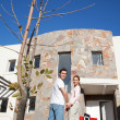 Happy couple in front of their new home — Stock Photo #5734791