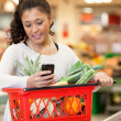 Smiling woman using mobile phone in shopping store — Stock Photo