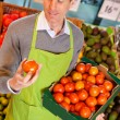 Постер, плакат: Grocery Store Clerk with Tomatoes