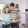 Couple going through house plan - Stock Photo