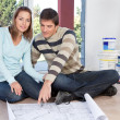 Couple sitting on the floor with blueprint of their new house - Stock Photo