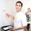 Smiling man painting the wall of his new apartment — Stock Photo
