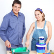 Portrait of happy couple with paint tools - Stock Photo