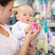 Mother with Baby in Supermarket - Stockfoto