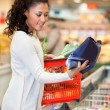 Smiling woman looking at product — Stock Photo #5735256