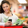 Woman with Shopping List on Phone — Stock Photo