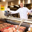 Fresh meat with cheerful butcher - Stock Photo