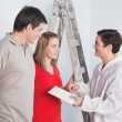 Workman suggesting colors to a mature couple — Stock Photo