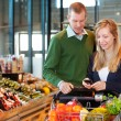 Couple Buying Groceries with List on Phone - Stock Photo