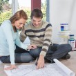 Man showing blueprint of their new house to his wife — Stock Photo