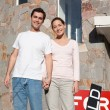 Happy young couple in front of their new home — Stock Photo