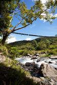 Berg rivier met opknoping van brug — Stockfoto